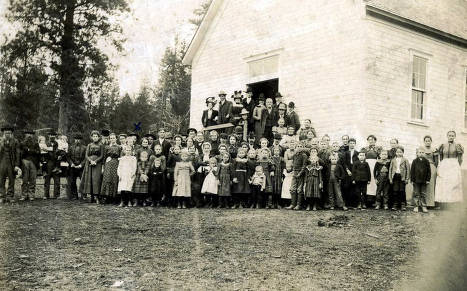 Sunday School group standing in front of church building in Avon, Idaho.